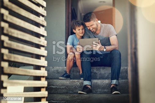 Shot of a father and son using a digital tablet together on the front steps of their home
