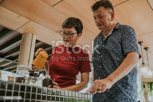 Craft coffee, Thai senior woman just teaching her husband for pouring water and making hot coffee drink at home, Thailand