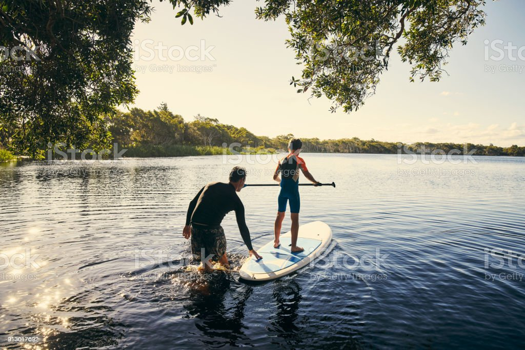 Teaching my boy how to paddle stock photo