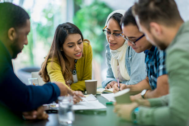 Teaching Office Workers A multi-ethnic group of business people are indoors in an office boardroom. They are sitting around a table and making plans. An Ethnic woman is explaining papers to her coworkers. immigrant stock pictures, royalty-free photos & images