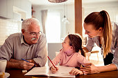 Close up of a grandfather helping out his granddaughter with schoolwork