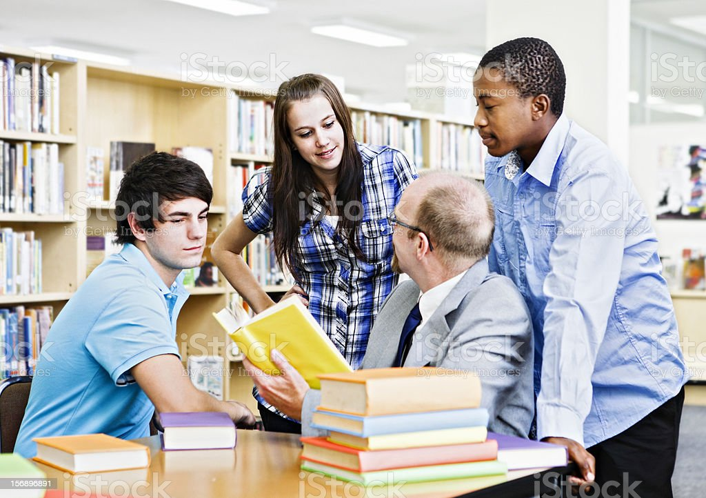 Teaching session with three students and professor in library interacting royalty-free stock photo