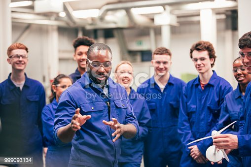 A tutor teaches his class about renewable energy in an engineering workshop. They are all wearing protective eyewear and blue coveralls.