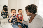 A woman is teaching the two boys how to brush their teeth.