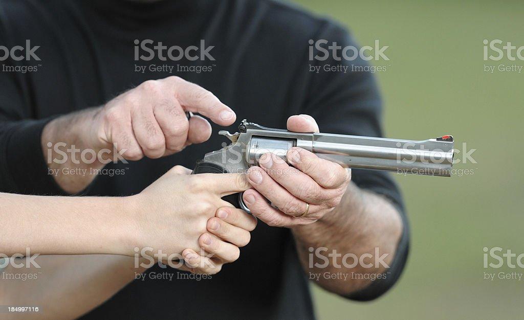 Teaching young person how to aim handgun stock photo