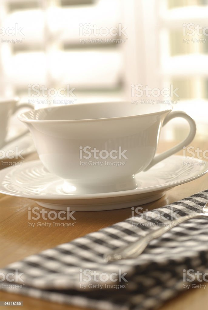 Teacup and saucer on a table with a tea towel next to them stock photo