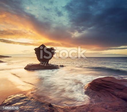 A striking rock formation known locally as the 'Teacup' silhouetted against a dramatic sunset on Prince Edward Island's North coast.  Long exposure, stitched images.