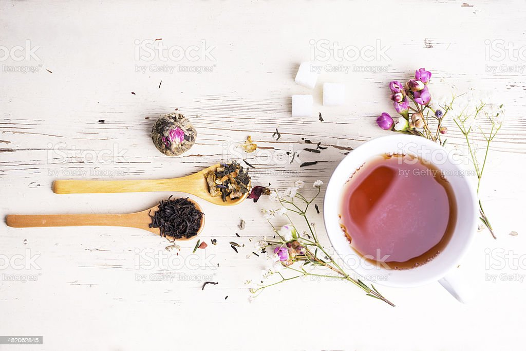 A teacup surrounded by flowers and tea leaves stock photo