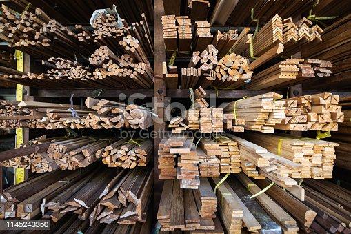 Teak wook boards in carpentry workshop of Golden Mount region in Bangkok, Thailand. Pattern of bars on the shelf.