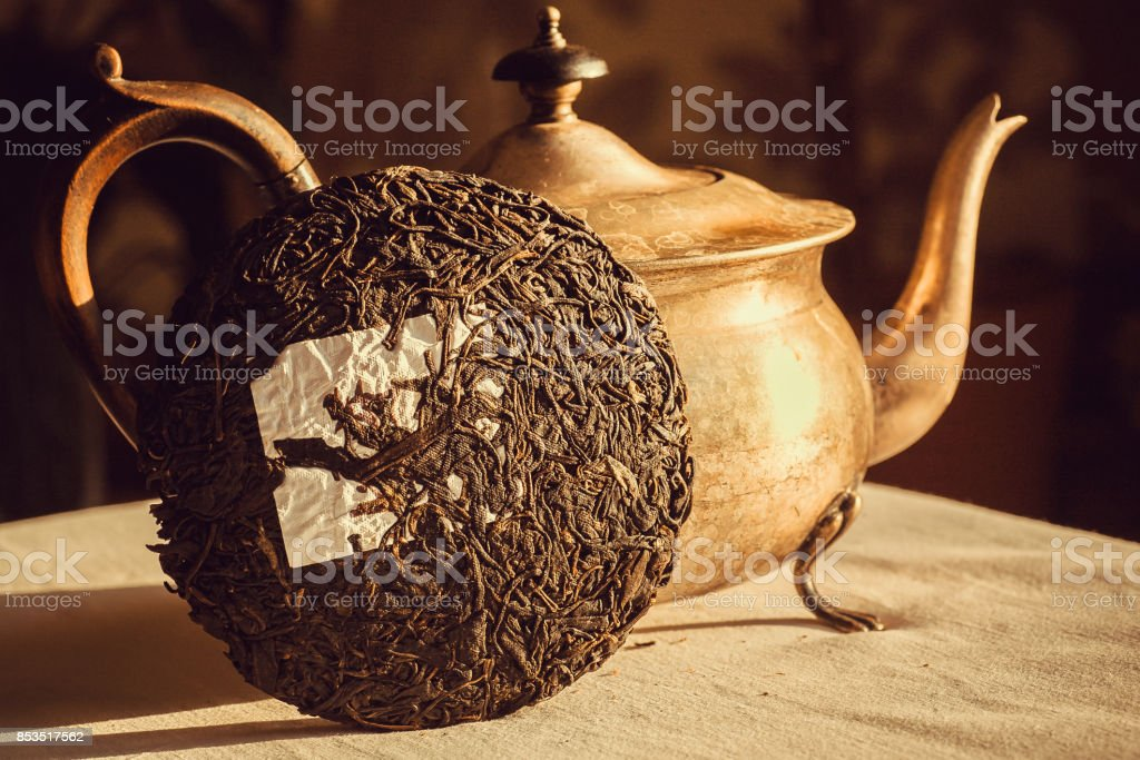 Teakettle with Pu-erh tea in shape of cake, traditional chinese drink. Popular antioxidant tea from China at kitchen table. stock photo