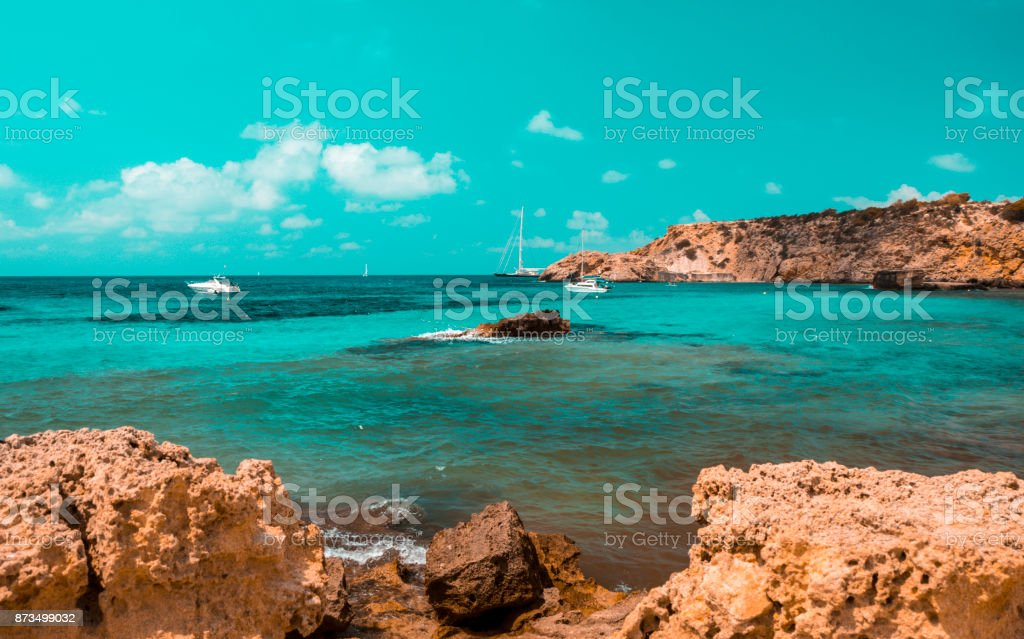 Blaugrün und orange Stimmung der Cala Tarida Beach mit Stein Felsen, Insel Ibiza. Spanien – Foto