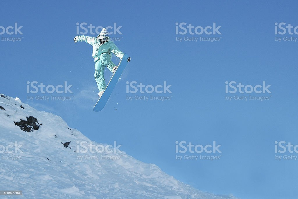 Teal Blue snowboarder catches air nose grab. Lots of copyspace. stock photo