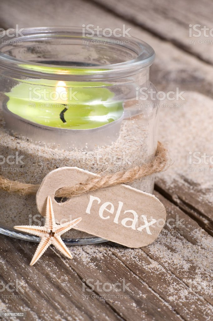 Tealight glass at the beach with lettering relax stock photo