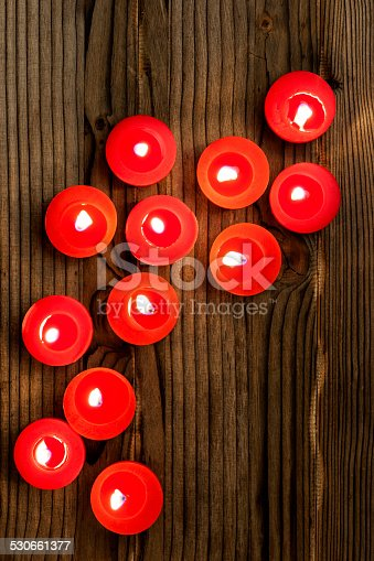 Red candles on wood background.