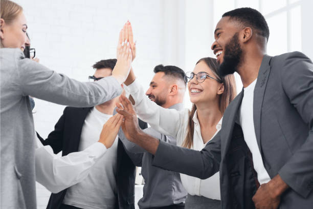 team achievement, diverse business people giving high five - business celebration stock pictures, royalty-free photos & images
