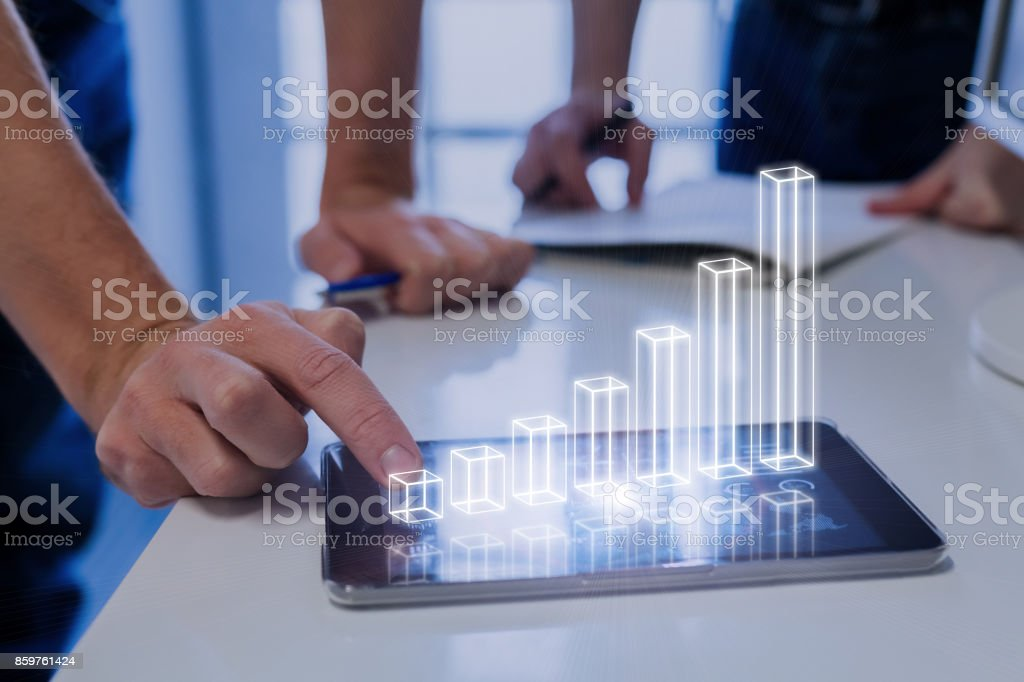 Team analyzing 3D AR chart, tablet computer, growing chart, investment success stock photo