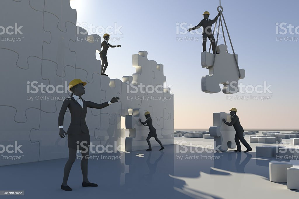 Team assembling a jigsaw puzzle in daylight stock photo