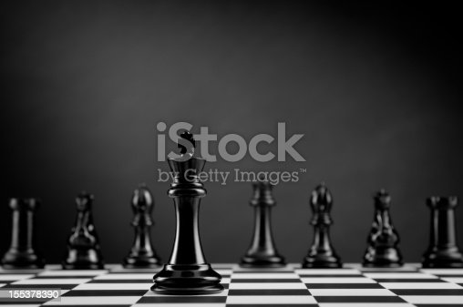 Leader and competition. Black Chess King on chess board against Chess Pieces on dark background.