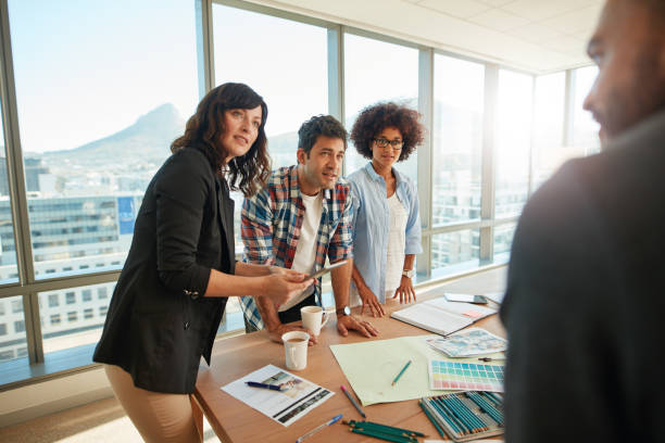 Team brainstorming over new designs in office stock photo