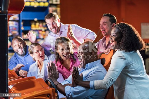 A multi-ethnic group of adults in an amusement arcade playing a video game. They are part of a group of people participating in corporate team building activities.  A mature African-American man in his 50s is in the driver's seat and his friends and coworkers are standing around him, cheering victory with high-fives.