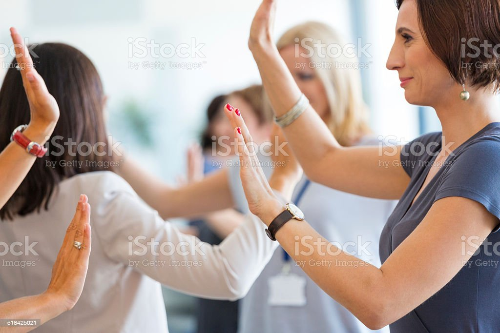 Team building Group of women attending a training, playing with hands together. 30-39 Years Stock Photo