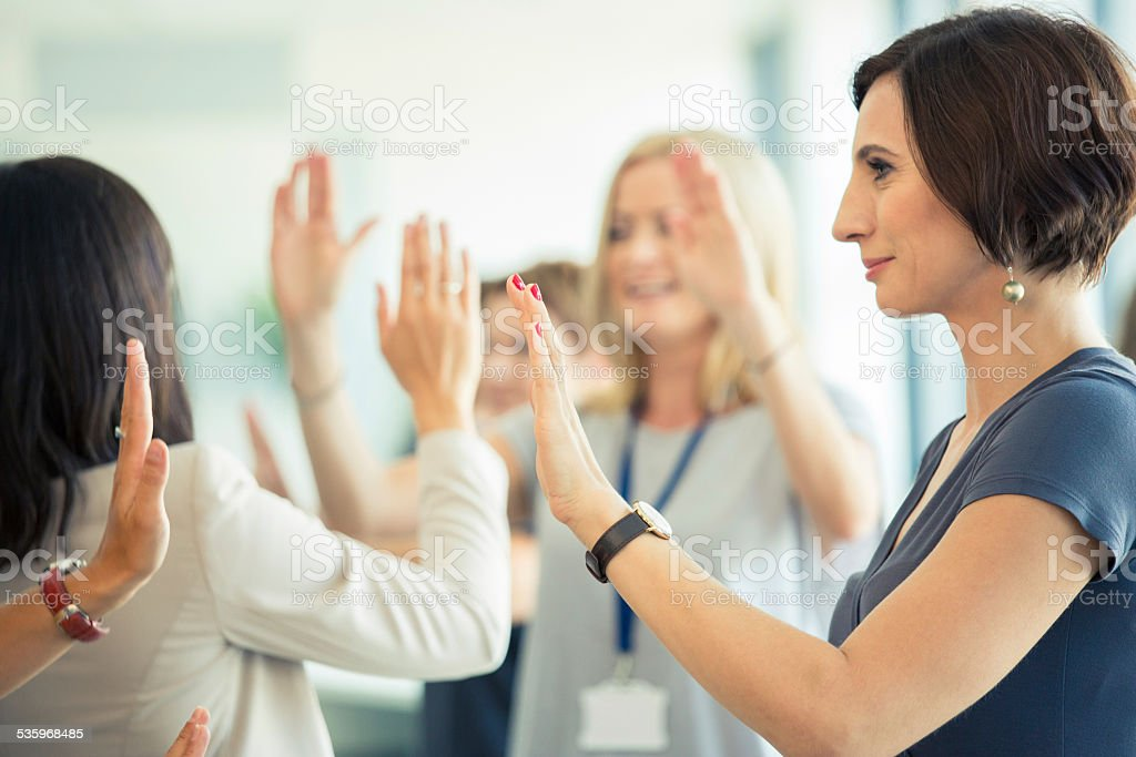 Team building workshop for women Group of women attending a training, playing with hands together. 2015 Stock Photo