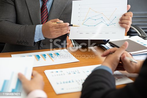 istock Team business analysts make decisions about the US economy that affect future operations of the company.concept 1194497421