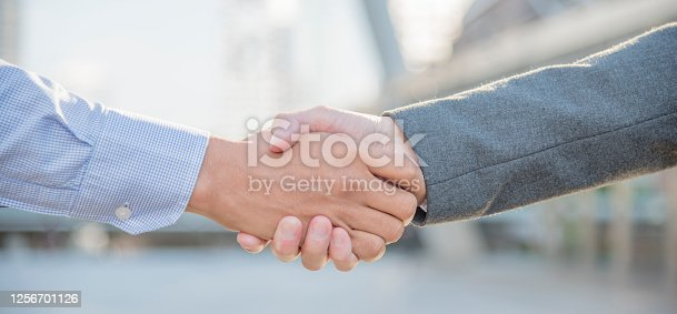 623122018 istock photo Team Business Partners shaking hands together to Greeting Start up new project. Corporate Teamwork Partnership outside office modern city as background. Businessman with Hands together. 1256701126