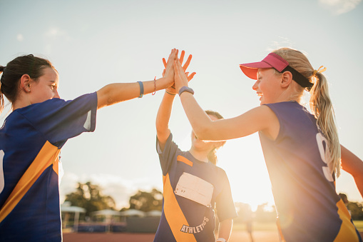 Three girls are high-fiving after a race at athletics club.