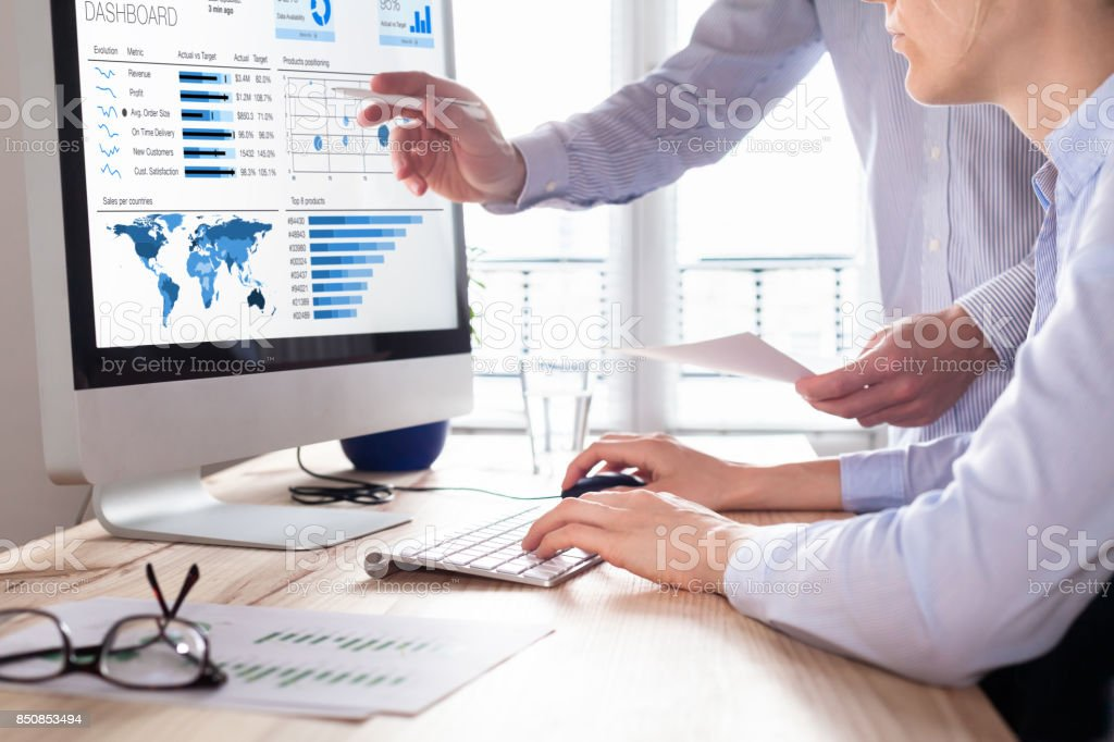 Team discussing business analytics or intelligence dashboard on computer screen stock photo
