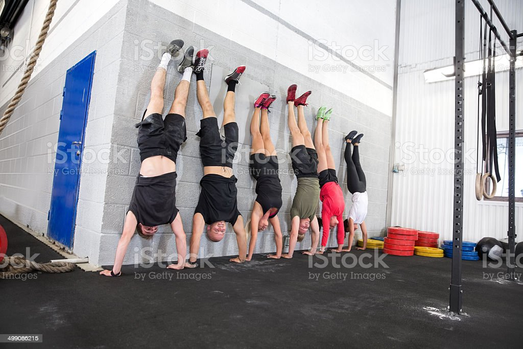 Team exercising handstands at fitness gym center stock photo