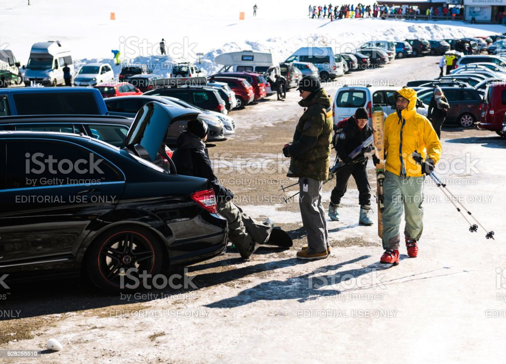 Snowboarders resting after game seated on a Mercedes-Benz fast car...