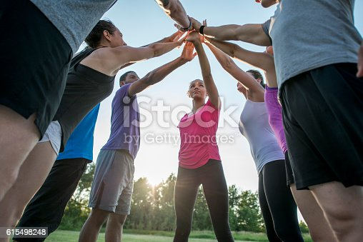 A multi-ethnic group of adults are taking an outdoor fitness class together at the park. They are standing together in a huddle and have their hands together in the middle.