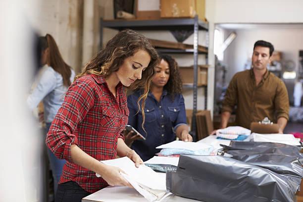 team in a post room packing clothes orders for distribution - kleidung amerikanischer ureinwohner stock-fotos und bilder
