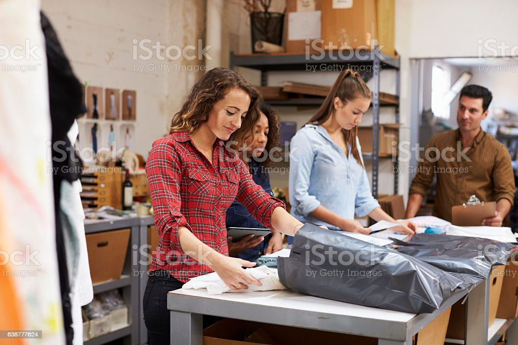 Team in a post room packing clothes orders for distribution stock photo