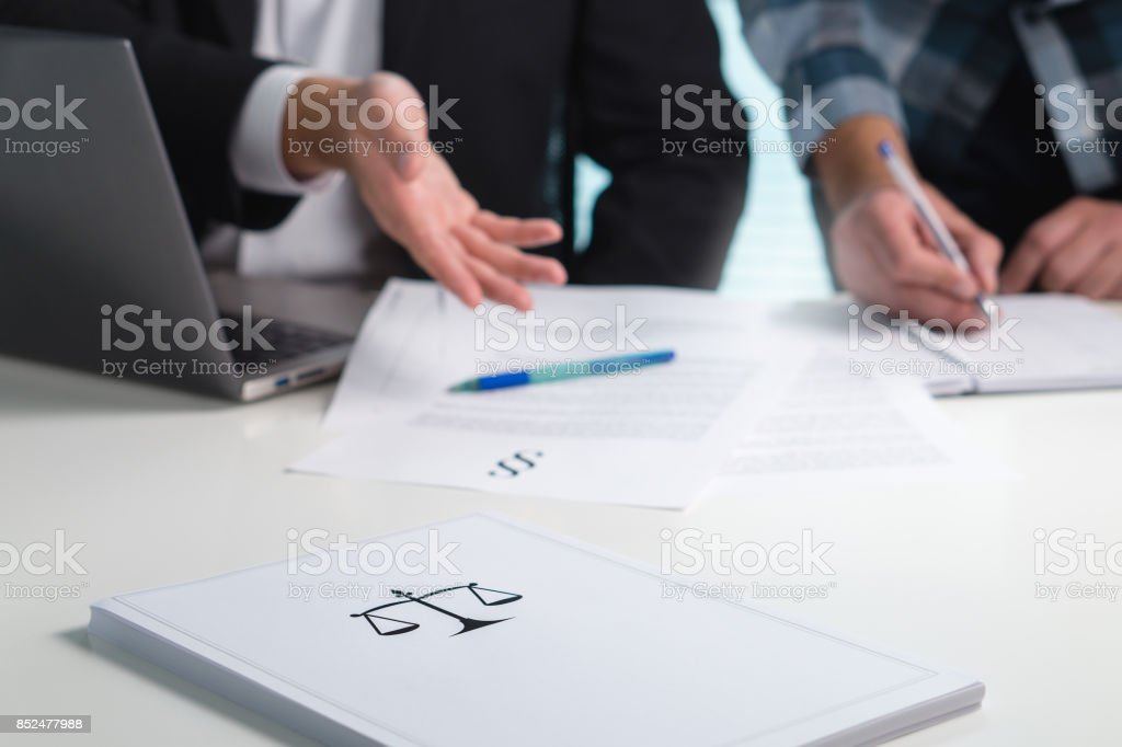 Team in law firm working in office. Lawyers discussing and writing. Business people having legal meeting. Pile of paper on table with scale and justice symbol. stock photo