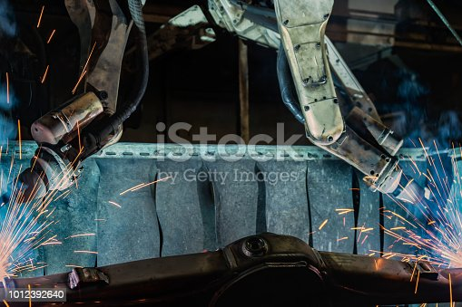 693576566 istock photo Team industrial robots are welding in factory 1012392640