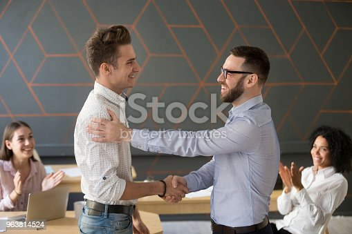878220300 istock photo Team leader handshaking employee congratulating with professional achievement or promotion 963814524