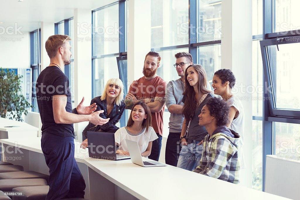 Team leader leading meeting in an office Multi ethnic business team having meeting in an office and listening to their leader.  2015 Stock Photo