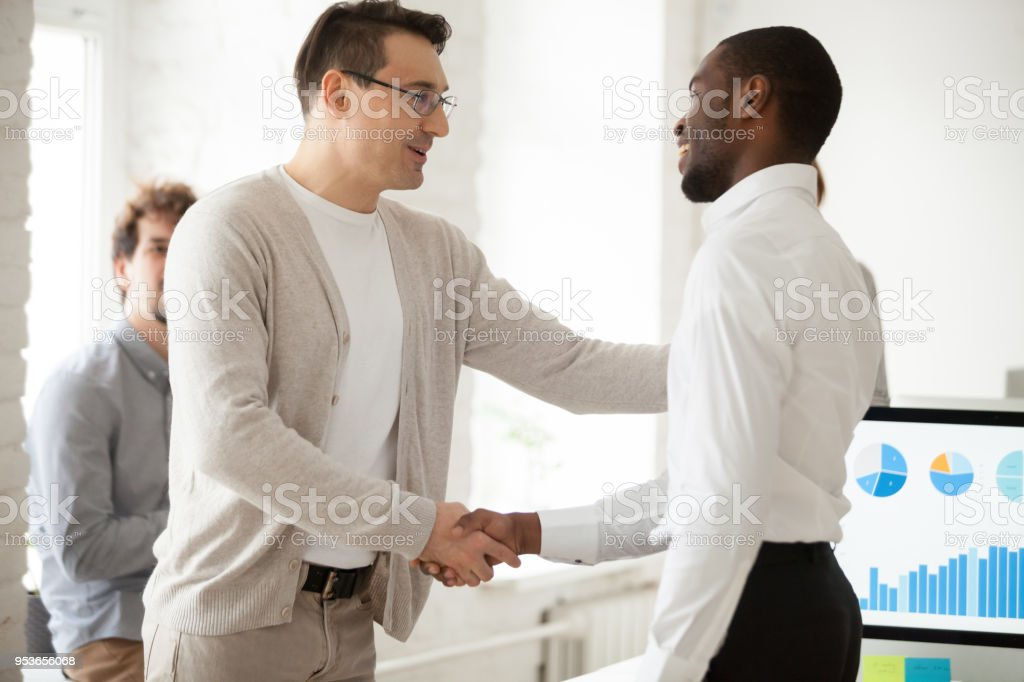 Team leader or boss promoting successful manager handshaking expressing gratitude stock photo