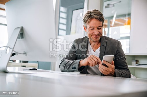 Mature team leader using his smartphone to text his team mates about new meeting times from his desk in the open office.