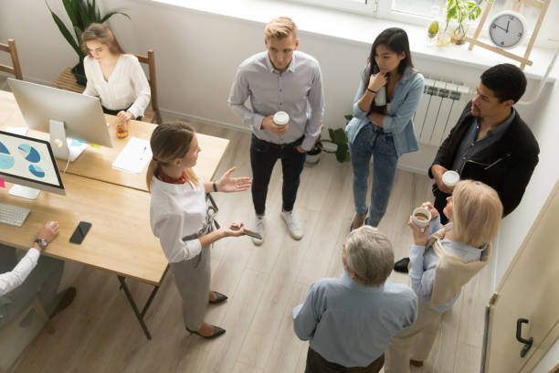 Team leaders meet multiracial interns in coworking office, top view stock photo