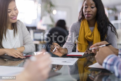 A multiethnic business team gathers around a conference table in a large open work space to finalize plans for the launch of their new startup. An African-American female is leading the meeting with several others.