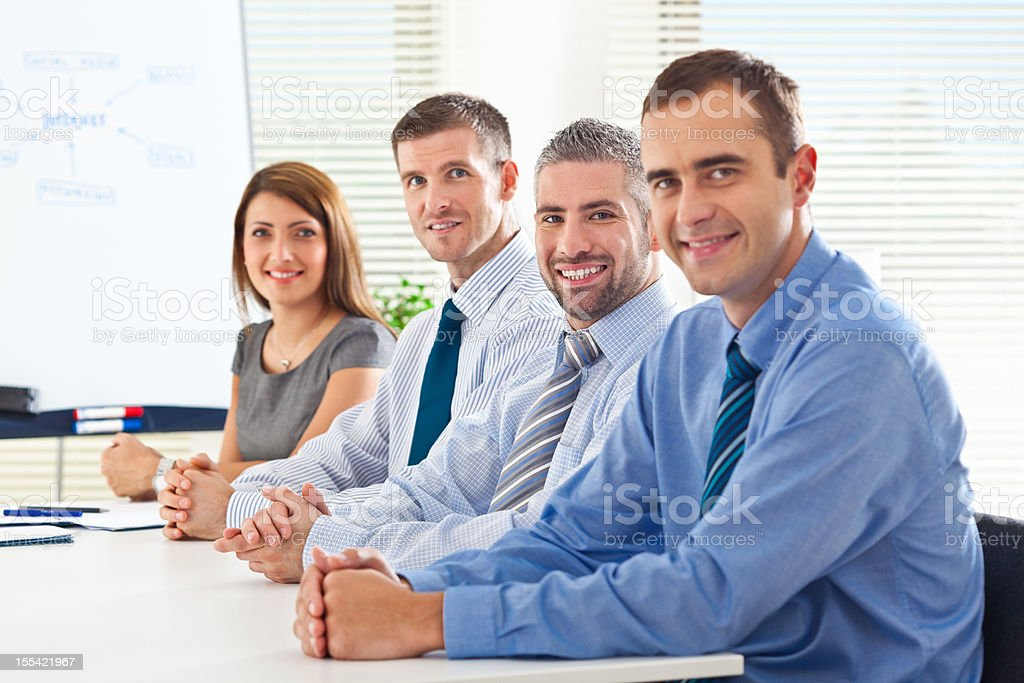Team meeting Four happy business people during business meeting in board room smiling at the camera. Adult Stock Photo