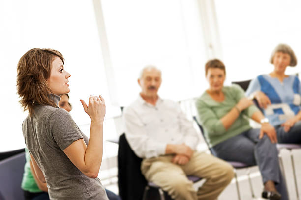 Team Meeting Adult education female teacher in front of her class. debate stock pictures, royalty-free photos & images
