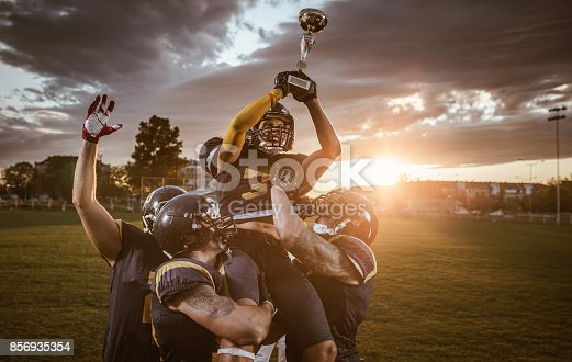 istock Team of American football players celebrating victory at sunset. 856935354