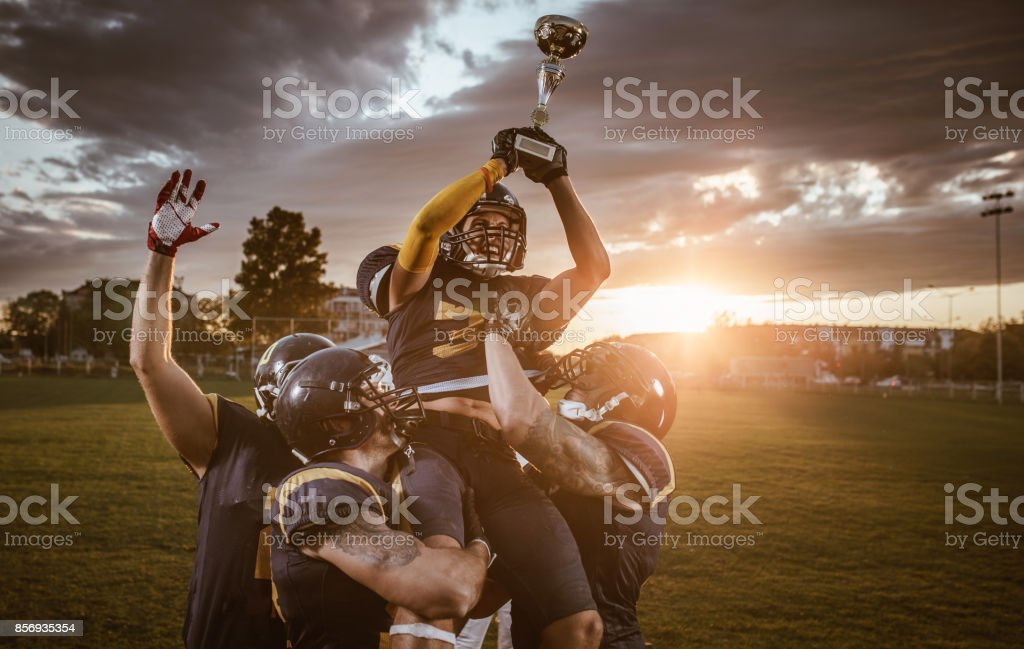 Team of American football players celebrating victory at sunset. stock photo