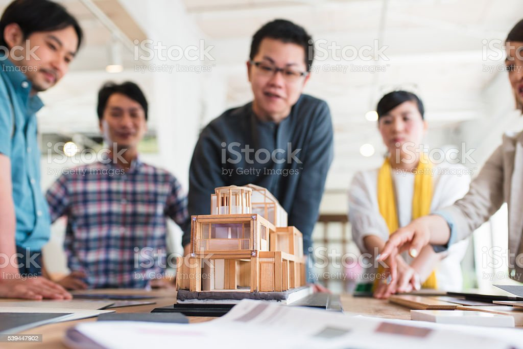 Team Of Architects Looking At A 3d Model Stock Photo & More