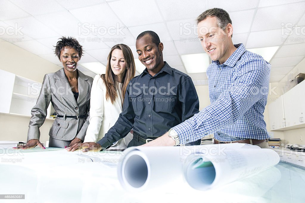 Team of Architects working on blueprints stock photo