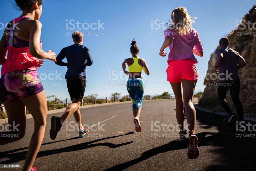Team of athletes running outdoors on summer stock photo